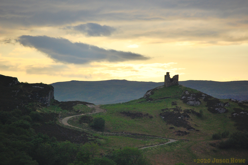 Castle ruin on top of a hill at sunset